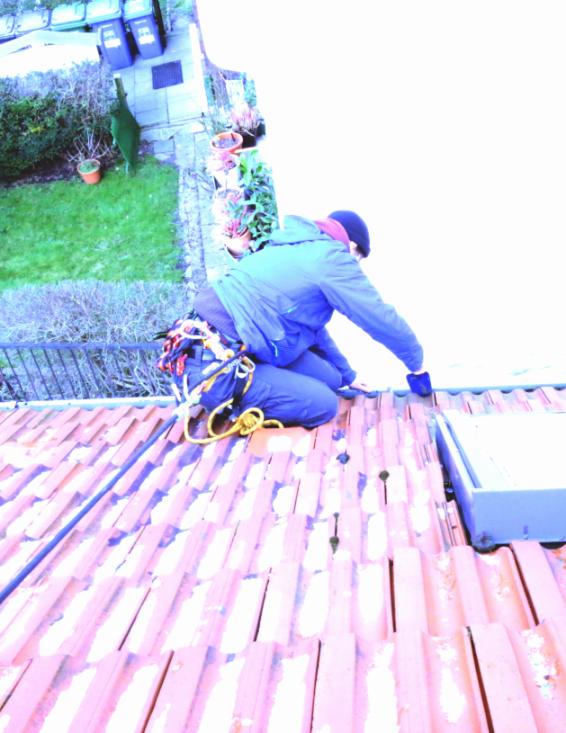 Person auf dem Dach, arbeitet an der Regenrinne