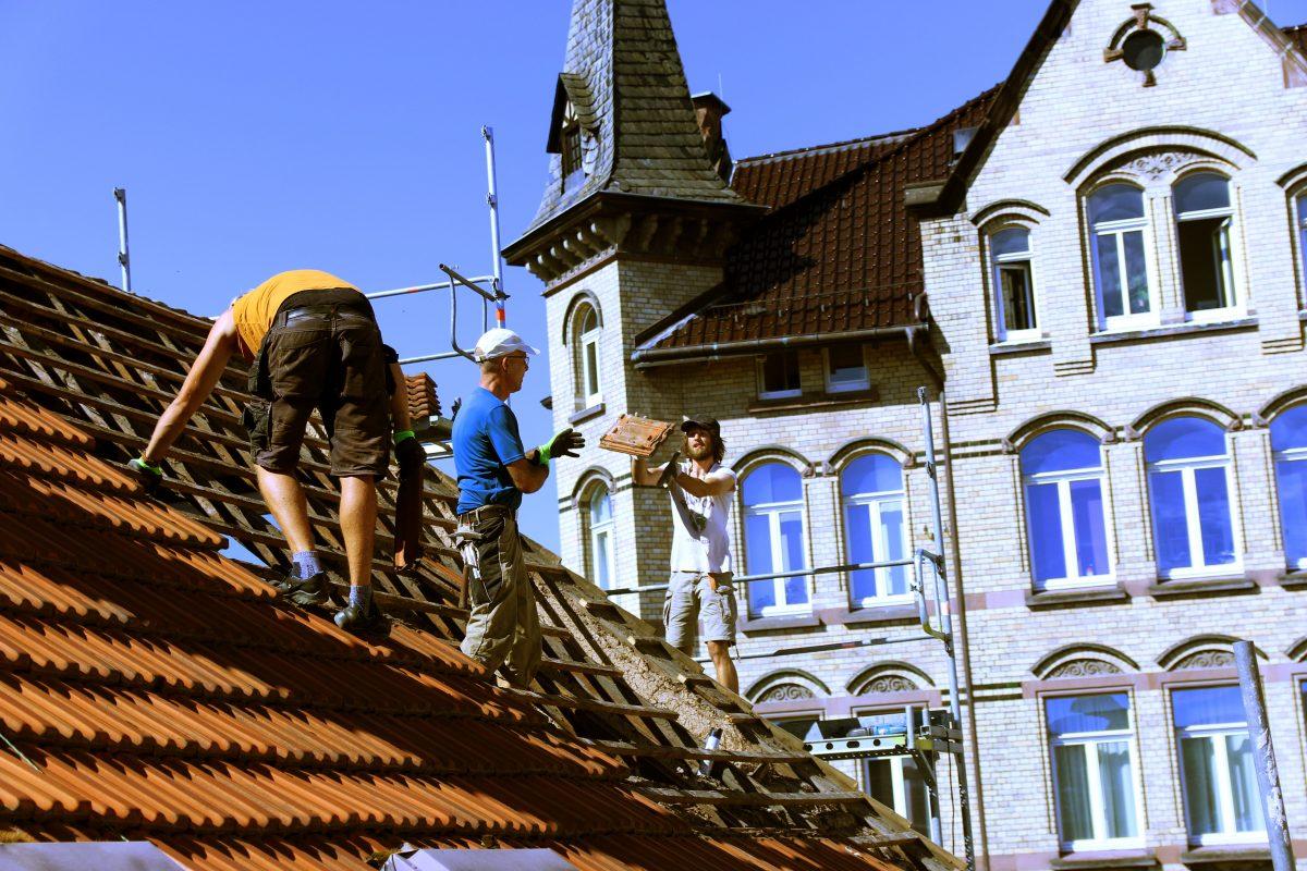 Dacharbeiter wirft einem Helfer einen Dachziegel zu