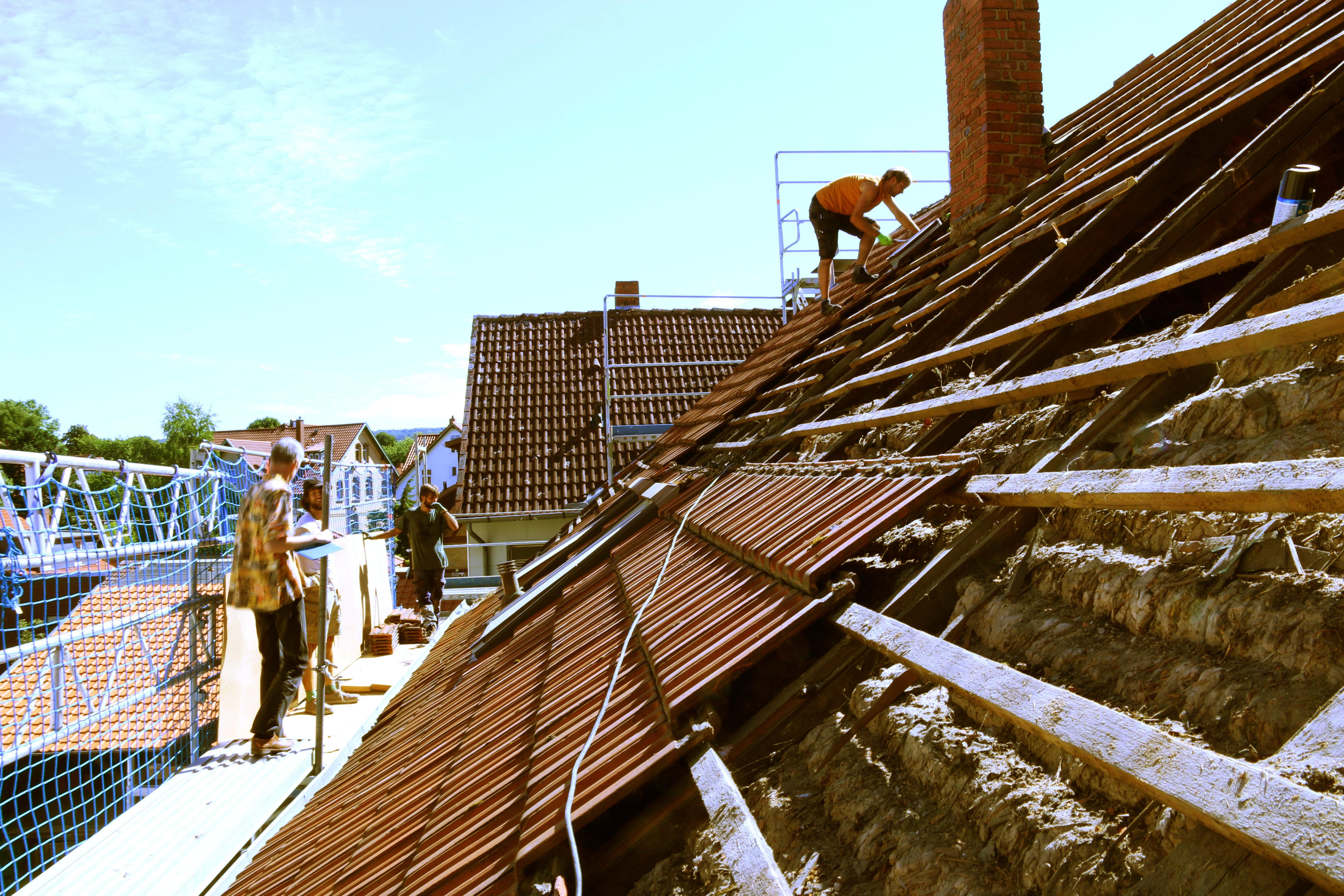 Halb abgedecktes Dach mit sichtbaren Lehmwickeln.
